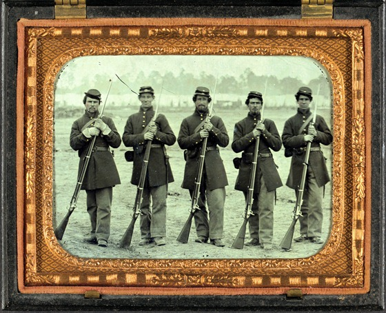 Five soldiers, four unidentified, in Union uniforms of the 6th Regiment Massachusetts Volunteer Militia outfitted with Enfield muskets in front of encampment