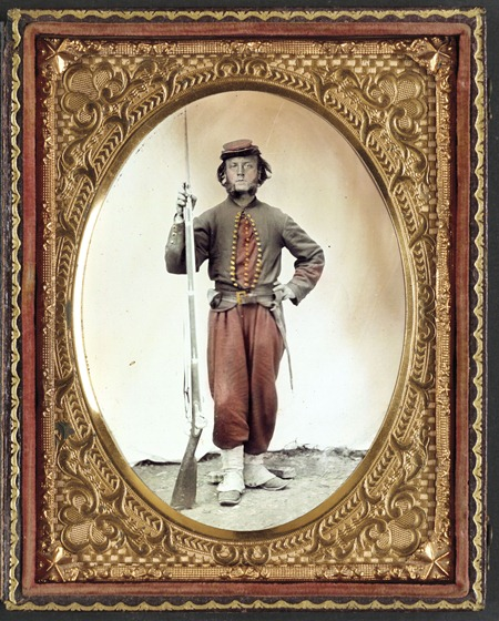 soldier in Union zouave uniform with bayoneted musket with initials A.T. on stock