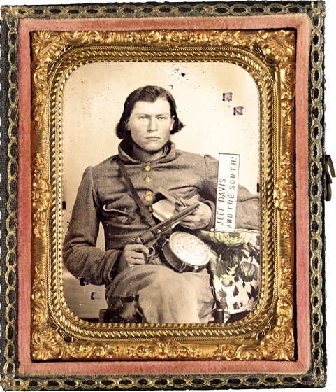 Thomas Isaiah Booker in Confederate uniform with Colt navy revolver, book, tin drum canteen, and sign reading Jeff Davis and the South!