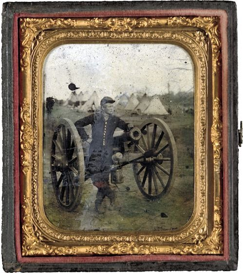 Unidentified soldier standing with Napoleon cannon in front of encampment