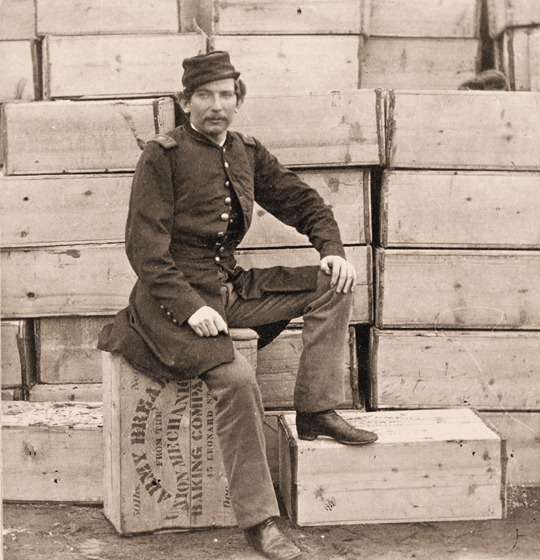 Union Captain J. W. Forsyth, the Provost Marshall, sitting on a crate of hardtack
