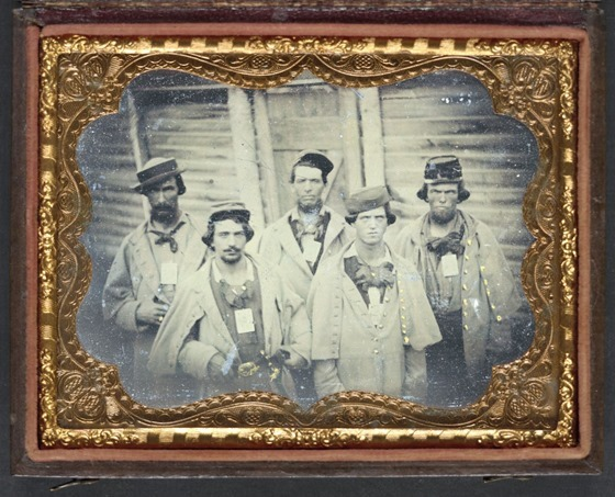 Five unidentified prisoners of war in Confederate uniforms in front of their barracks at Camp Douglas Prison, Chicago, Illinois
