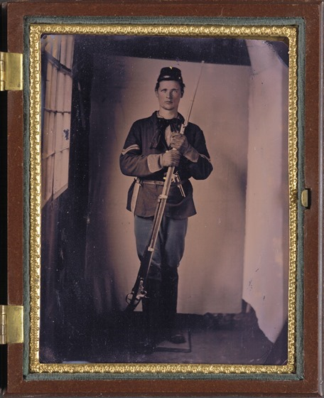 Unidentified soldier in Union uniform with M1816 conversion musket with affixed bayonet, bowie knife, and large Colt revolver