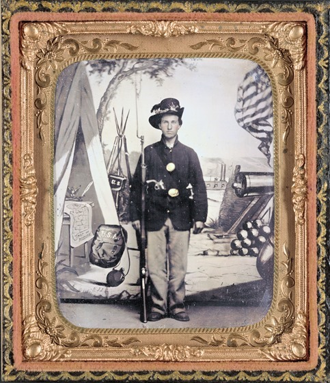 Unidentified soldier of 33rd Missouri Infantry Regiment with bayoneted musket and revolver in front of painted backdrop showing weapons and American flag at Benton Barracks, Saint