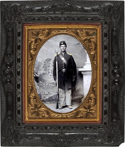 Unidentified soldier in Union frock coat and shoulder scales with bayoneted musket, cap box, and cartridge box in front of painted backdrop showing lake and trees in frame