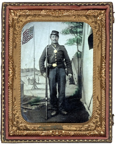 Unidentified soldier in Union uniform with bayoneted musket, canteen, cartridge and cap boxes in front of painted backdrop showing military camp with American flag in photo case