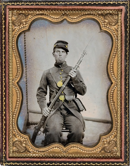 Unidentified soldier in Union uniform with bayoneted musket, cartridge box, and cap box in photo case