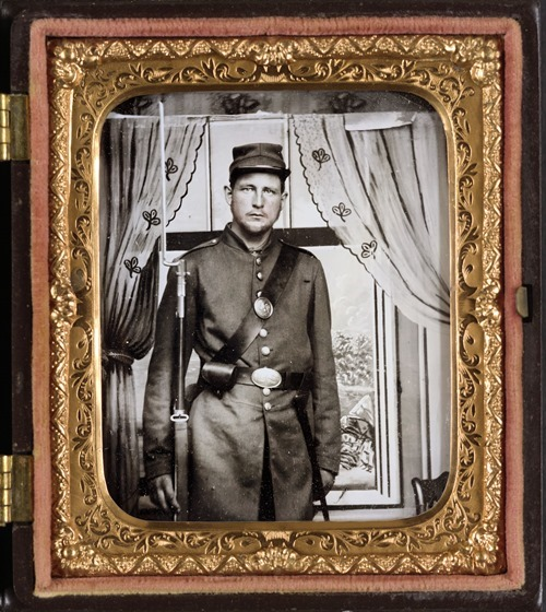 Unidentified soldier in Union uniform with bayoneted musket in front of painted backdrop showing a window with curtains in photo case