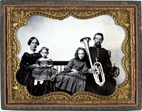 Unidentified soldier in Union uniform with wife and daughters holding saxhorn in photo case