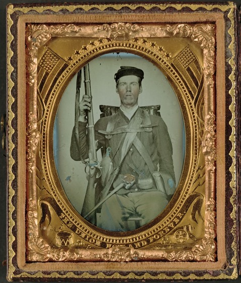 Unidentified infantry soldier in Union uniform in full marching order with musket, canteen, cartridge box, cap box, and knapsack in case