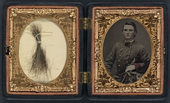 Unidentified soldier in Confederate artillery first lieutenant's uniform holding sword, with lock of hair in case