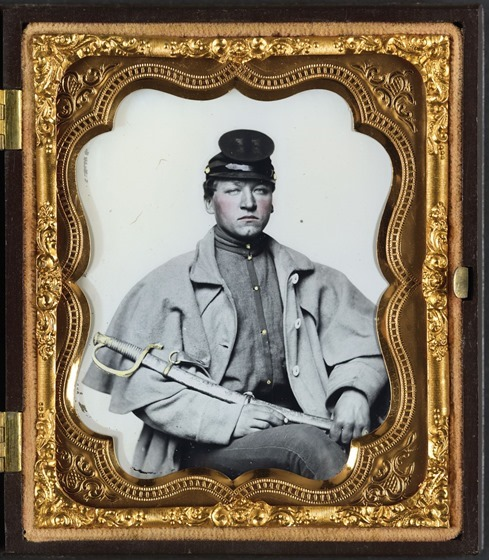 Unidentified soldier in Confederate artilleryman uniform and greatcoat with sword in case