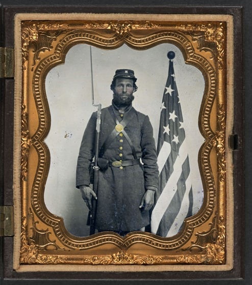 Unidentified soldier in Union uniform and Company H cap with bayoneted musket, cap box, and Volunteer Maine Militia (VMM) belt buckle in front of American flag in case