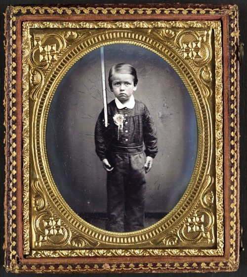 Unidentified young boy wearing secession badge and holding a rifle
