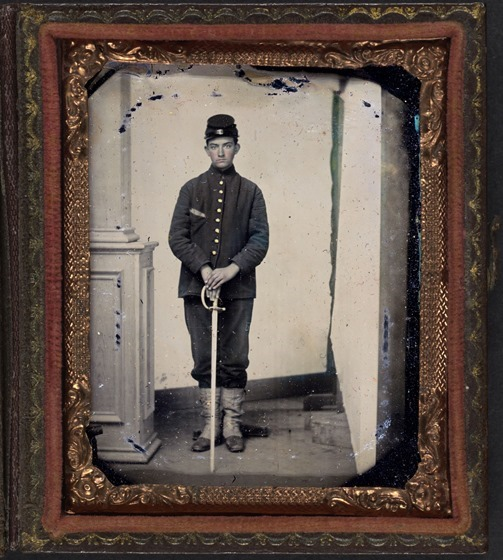 Unidentified young soldier in Union sack coat, forage cap, and white gaiters with sword -- fraamed
